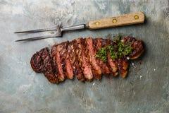 Bifteck coupé en tranches avec le chimichurri avec la fourchette de sauce et de viande à chimichurri image libre de droits
