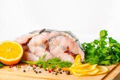 Bifteck coupé en tranches cru des poissons d'esturgeon avec des verts, citron, différent image stock