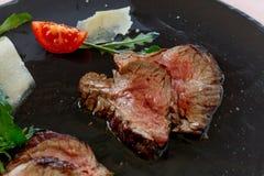 Bifteck coupé en tranches d'un plat noir avec les tranches de tomate et le parmesan photographie stock libre de droits
