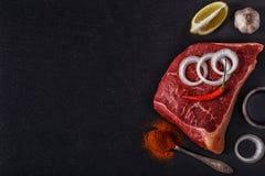 Bifteck cru avec des épices et des ingrédients pour la cuisson Images stock