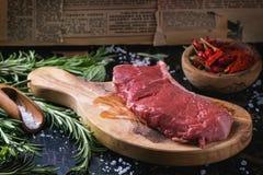Bifteck cru avec les herbes et le poivre Photographie stock libre de droits