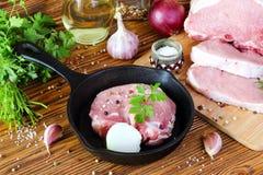 Bifteck cru de porc dans une poêle photo stock
