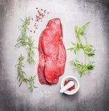 Bifteck cru de viande de boeuf avec les herbes fraîches sur le fond en pierre gris photographie stock libre de droits