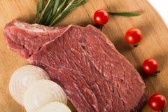Bifteck cru frais à l'oignon, aux tomates et au romarin du plat en bois images stock