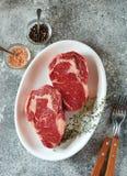 Bifteck cru juteux avec le thym sur un fond gris Nourriture saine organique Vue sup?rieure image libre de droits