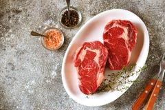 Bifteck cru juteux avec le thym sur un fond gris Nourriture saine organique Vue sup?rieure photographie stock libre de droits