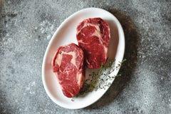 Bifteck cru juteux avec le thym sur un fond gris Nourriture saine organique Vue sup?rieure image stock