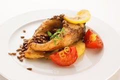 Bifteck cuit au four de carpe sur des pommes de terre, des lentilles, des tomates et le zeste de citron Photographie stock libre de droits