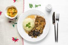 Bifteck cuit de côtelette de porc avec les champignons et la purée de pommes de terre sur le whi Photo libre de droits