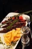 Bifteck délicieux avec des légumes sur un fond foncé Image stock