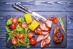 Bifteck d'agneau de BBQ avec de la salade et le maïs végétaux sur le dos en bois foncé Images libres de droits