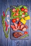 Bifteck d'agneau de BBQ avec de la salade et le maïs végétaux sur le dos en bois foncé Photographie stock libre de droits
