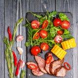 Bifteck d'agneau de BBQ avec de la salade et le maïs végétaux sur le dos en bois foncé Photo libre de droits