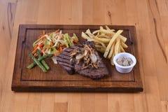 Bifteck d'une plaque en bois Photos libres de droits