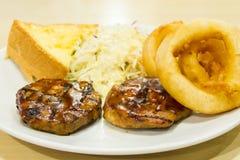 Bifteck de boeuf avec des anneaux d'oignon, fritures Photographie stock