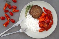 Bifteck de boeuf avec du riz, tomate, poivre bulgare d'un plat noir au restaurant Type rustique Fond en pierre gris photo libre de droits