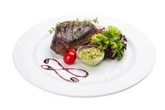 Bifteck de boeuf avec de la sauce à guacamole D'un plat blanc images stock
