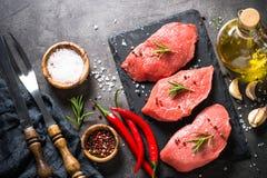 Bifteck de boeuf avec le romarin et les épices sur le fond noir Image stock