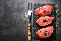 Bifteck de boeuf avec le romarin et les épices sur le fond noir Photos libres de droits