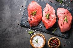 Bifteck de boeuf avec le romarin et les épices sur le fond noir Images stock