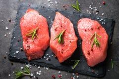 Bifteck de boeuf avec le romarin et les épices sur le fond noir Photographie stock