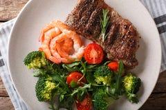 Bifteck de boeuf avec les crevettes roses et le brocoli, tomates, plan rapproché o d'arugula images stock