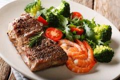 Bifteck de boeuf avec les crevettes roses et le brocoli, tomates, plan rapproché o d'arugula photos libres de droits