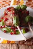 Bifteck de boeuf avec les graines de grenade et le plan rapproché de basilic vertical Photo libre de droits