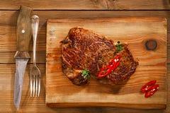 Bifteck de boeuf avec les piments rouges sur le bois et la table Images stock