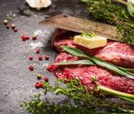 Bifteck de boeuf cru Préparation avec le vieux fendoir de viande, le beurre et les herbes fraîches photos libres de droits