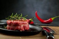 Bifteck de boeuf cru sur une table en bois foncée images libres de droits