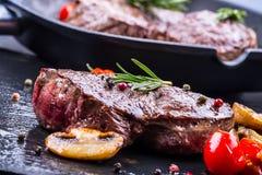 Bifteck de boeuf de gril Biftecks d'aloyau juteux de boeuf épais de parties sur la casserole de téflon de gril ou le vieux consei Photo libre de droits