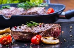Bifteck de boeuf de gril Biftecks d'aloyau juteux de boeuf épais de parties sur la casserole de téflon de gril ou le vieux consei Image libre de droits