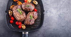 Bifteck de boeuf de gril Biftecks d'aloyau juteux de boeuf épais de parties sur la casserole de téflon de gril ou le vieux consei Images libres de droits