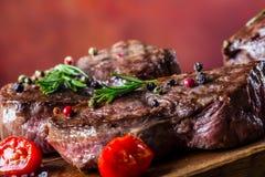 Bifteck de boeuf de gril Biftecks d'aloyau juteux de boeuf épais de parties sur la casserole de téflon de gril ou le vieux consei Images stock