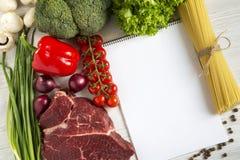 Bifteck de boeuf frais de viande crue avec le poivre, tomates-cerises, spaghetti italiens, nourriture biologique, vue supérieure photos libres de droits