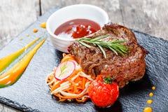 Bifteck de boeuf grillé avec de la salade fraîche et la sauce à BBQ sur le fond en pierre d'ardoise sur la fin en bois de fond  Image libre de droits