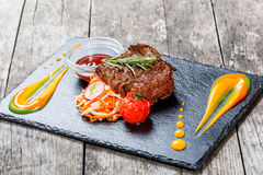 Bifteck de boeuf grillé avec de la salade fraîche et la sauce à BBQ sur le fond en pierre d'ardoise sur la fin en bois de fond  Image stock