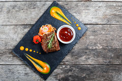 Bifteck de boeuf grillé avec de la salade fraîche et la sauce à BBQ sur le fond en pierre d'ardoise sur la fin en bois de fond  P Photographie stock libre de droits