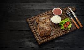Bifteck de boeuf grillé avec des sauces sur un conseil Table en bois foncée Images libres de droits