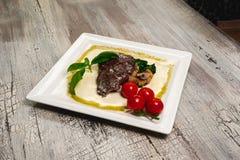 Bifteck de boeuf grillé avec des tomates et des champignons Images libres de droits