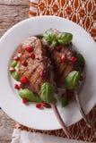 Bifteck de boeuf grillé avec la grenade et le plan rapproché de basilic vertical Photo libre de droits