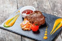 Bifteck de boeuf grillé avec de la salade fraîche et la sauce à BBQ sur le fond en pierre d'ardoise sur le fond en bois Images libres de droits