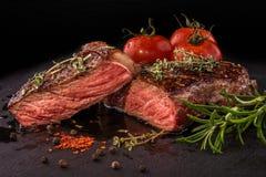 Bifteck de boeuf grillé coupé en tranches avec des épices sur la dalle d'ardoise Photo stock