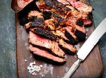 Bifteck de boeuf grillé coupé en tranches avec le couteau, sauce, sel sur la planche à découper en bois Images stock