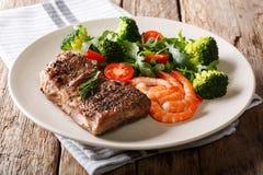 Bifteck de boeuf grillé délicieux avec les crevettes roses et le brocoli, tomates, photographie stock libre de droits