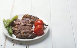 Bifteck de boeuf grillé d'un plat blanc et d'un fond blanc image libre de droits