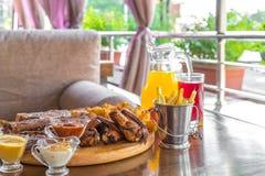 Bifteck de boeuf grillé et viande grillée délicieuse assortie avec et boissons fraîches sur la table de la véranda d'été photos stock