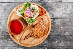Bifteck de boeuf grillé sur l'os, la salade fraîche, la sauce de légume et tomate grillée sur la planche à découper sur le fond e Image stock