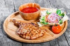 Bifteck de boeuf grillé sur l'os, la salade fraîche, la sauce de légume et tomate grillée sur la planche à découper sur le fond e Images stock